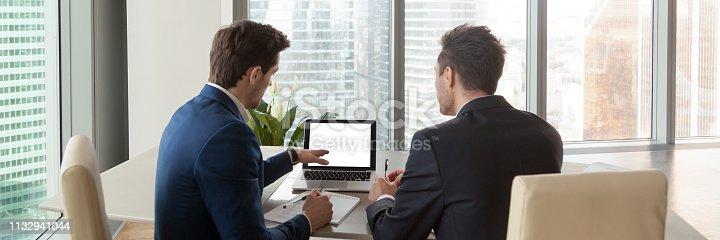 istock Horizontal rear image businessmen analyzing market pointing on computer screen 1132941044