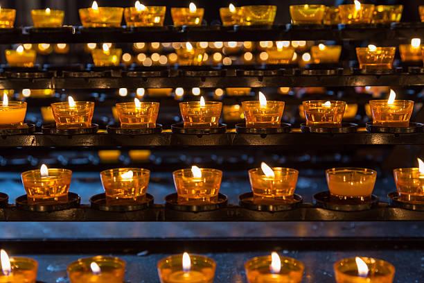 Horizontale Reihen Teelicht Kerzen brennen in einer Kirche – Foto