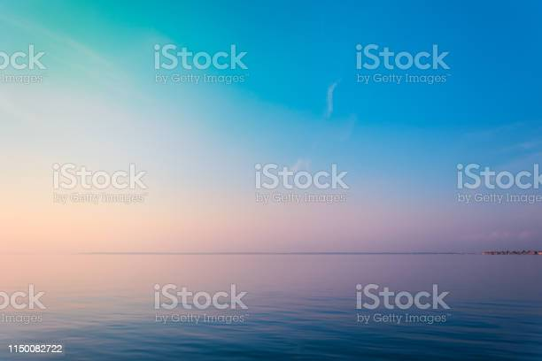 Photo of Horizontal sea line in the evening sunlight over sky background. Blue hour sunset. Summer adventure or vacation concept. Copy space.