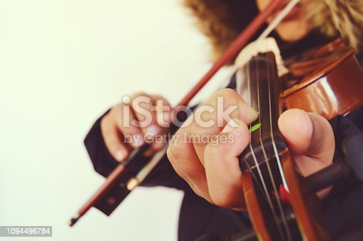 A child playing the stringed and bowed musical instrument, the violin, captured from the front. Right aligned in the horizontal shot. Empty copy space to the left.  Depth of field. The child is holding the violin bow in his hand, four fingers, and is pressing it against the strings in a beautiful pose.  There is a brown faux fur attached to the hood, hoodie of his black coat, jacket. Apt for Valentine / valentine's day, love greetings card, poster, sorry or Thank you, Propose, proposal message /  messages. No text. The bow stick is also over the child's lips.