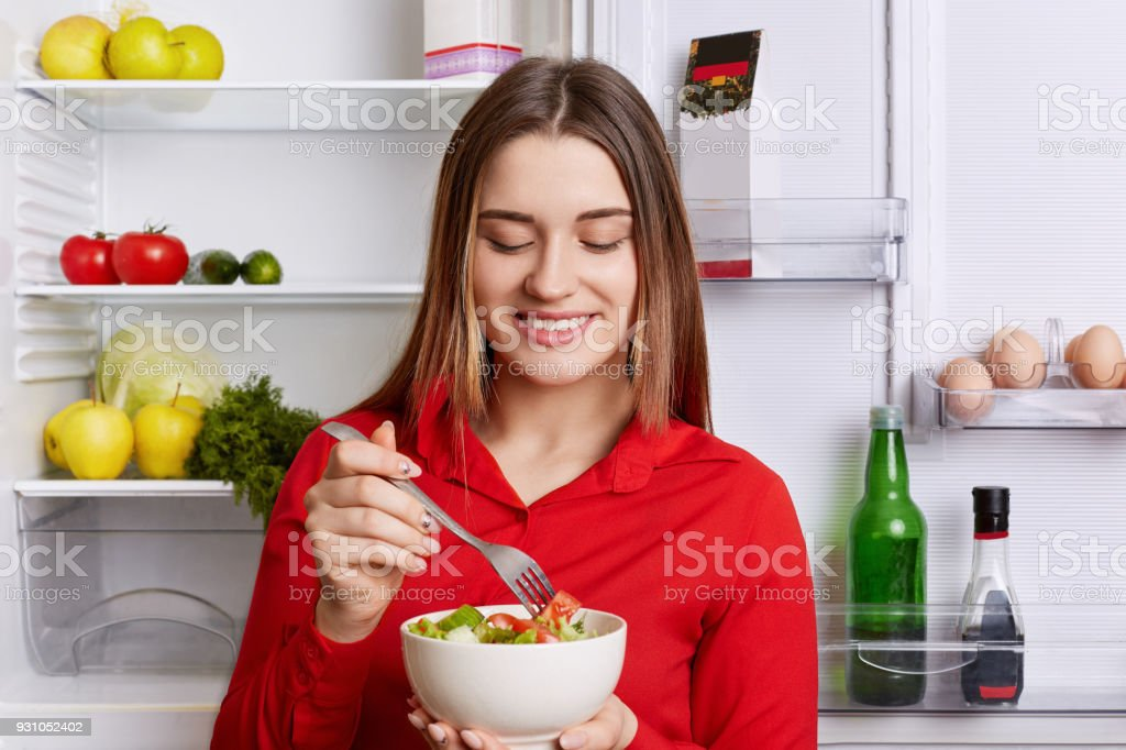 Horizontal shot of cheerful female holds bowl with fresh vegetable salad, stands near friedge full of products, keeps to diet. Woman vegeterian eats only raw products. Healthy eating concept stock photo
