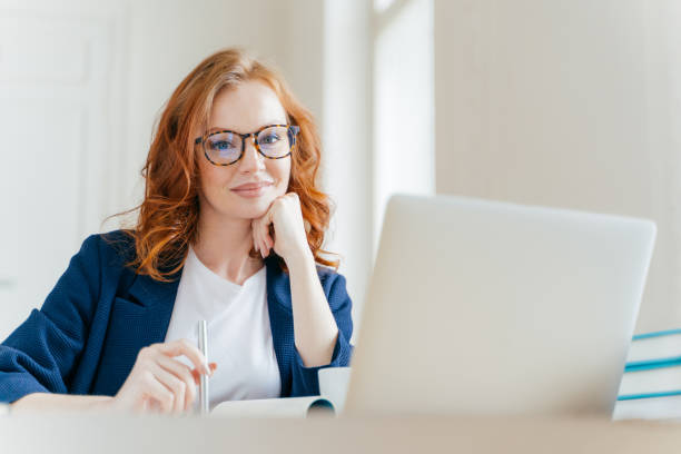 horizontal shot of pleasant looking successful professional female lawyer learns clients case, works on modern laptop computer, dressed in formal apparel and transparent glasses, poses in office - business woman foto e immagini stock
