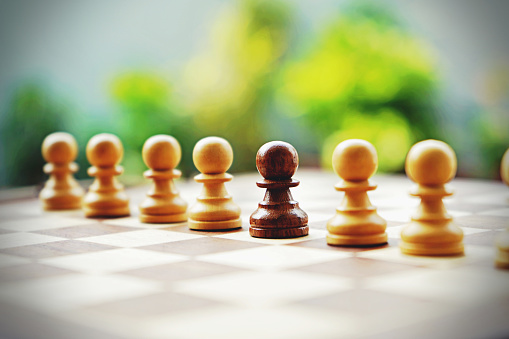 Horizontal stock photograph of one brown black colored pawn, an odd one out in a row of white pawns