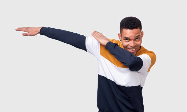 Horizontal studio shot of happy and charismatic African American young man making dab pulling hands right tilting, looking to the camera with broadly smile, dancing, having fun over white background stock photo