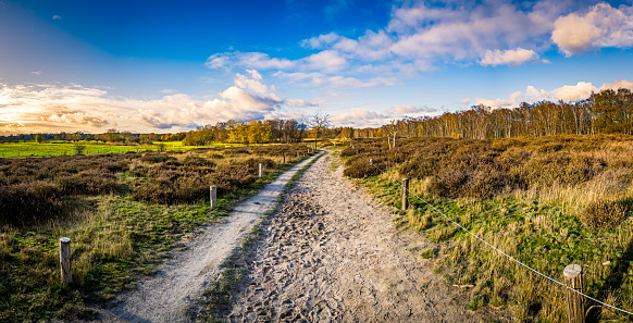 horizontal ultra wide angle panorama of a peaceful path outside in the landscape of a nature reserve in hamburg called boberger niederung during daytime in autumn with stunning cloudscape.