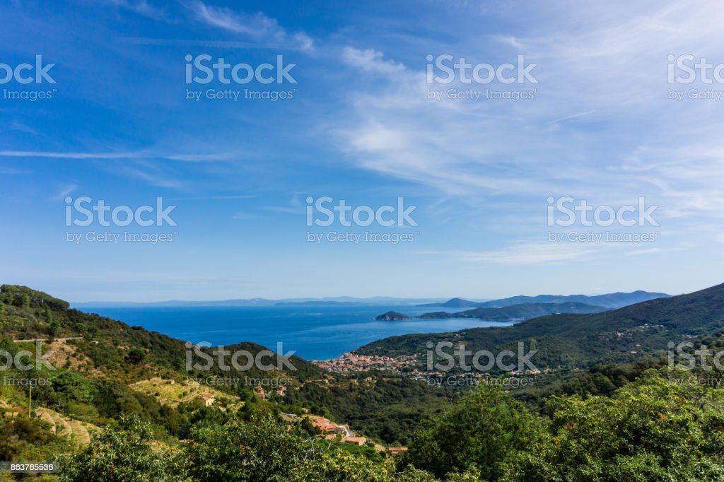 Horizontal view down on small town Marciana Marina on the coast of Elba island in Mediterranean sea. The hills and mountains around are covered by trees and bush. Sky is blue with few clouds. stock photo