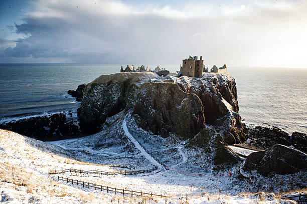 Horizontal View in Snow - Dunnottar Castle, Stonehaven, Scotland UK Dunnottar Castle is a ruined medieval fortress located upon a rocky headland on the north-east coast of Scotland, about 3 kilometers (1.9 mi) south of Stonehaven. The surviving buildings are largely of the 15th and 16th centuries, but the site is believed to have been fortified in the Early Middle Ages. Dunnottar has played a prominent role in the history of Scotland through to the 18th-century Jacobite risings because of its strategic location and the strength of its situation. Dunnottar is best known as the place where the Honours of Scotland, the Scottish crown jewels, were hidden from Oliver Cromwell's invading army in the 17th century. The property of the Keiths from the 14th century, and the seat of the Earl Marischal, Dunnottar declined after the last Earl forfeited his titles by taking part in the Jacobite rebellion of 1715. The castle was restored in the 20th century and is now open to the public. headland stock pictures, royalty-free photos & images