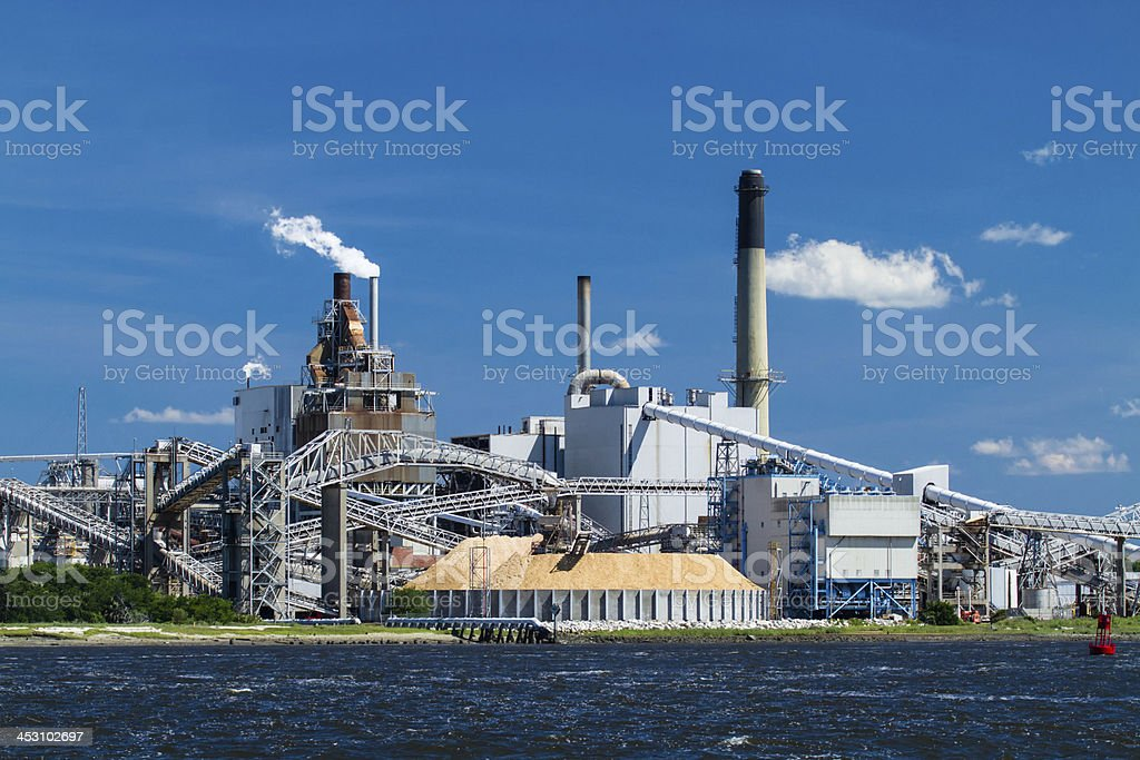A horizontal view of an industrial paper mill on a river stock photo