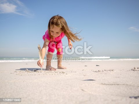 Horizontal View of Beautiful Little Girl Drawing with Feather in the Sand on Beach against Seascape with Clear Sky