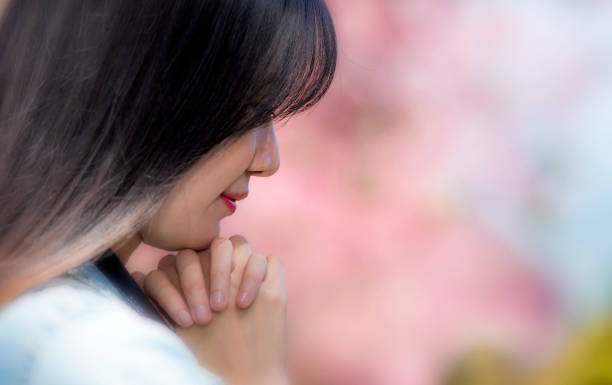 Horizontal view of young beautyful woman is in praying with soft pink color background stock photo