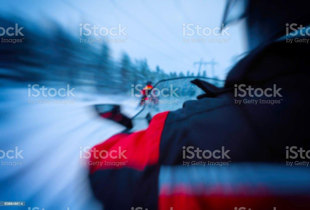 Horizontal vivid snowmobile rider blurred background stock photo
