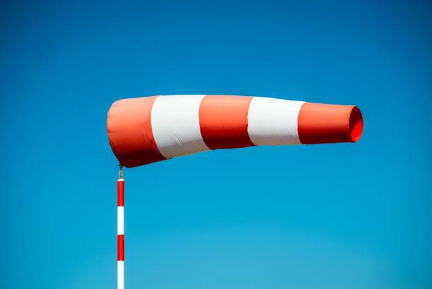 horizontal fliegenden windsack (windfahne) mit blauen himmel im hintergrund. - wettervorhersage deutschland stock-fotos und bilder