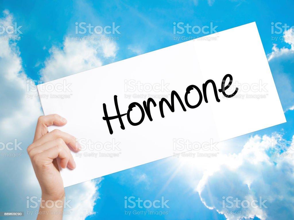 Señal de la hormona sobre papel blanco. Hombre mano sosteniendo el papel con el texto. Aislado sobre fondo de cielo - foto de stock