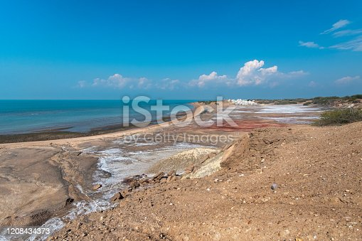 The image is taken in beautiful Hormuz Island, an Iranian island in Persian Gulf, Hormozgan Province. Hormuz Island is a dome-shaped salty island located in the Strait of Hormuz. The island is arid, covered by sedimentary rock and layers of volcanic material, and the mountains are beautifully colourful.