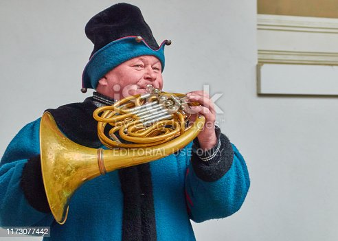 Dresden, Germany, December 14., 2018:Horn blower in a historical blue dress plays on the old horn outdoors in front of a white wall