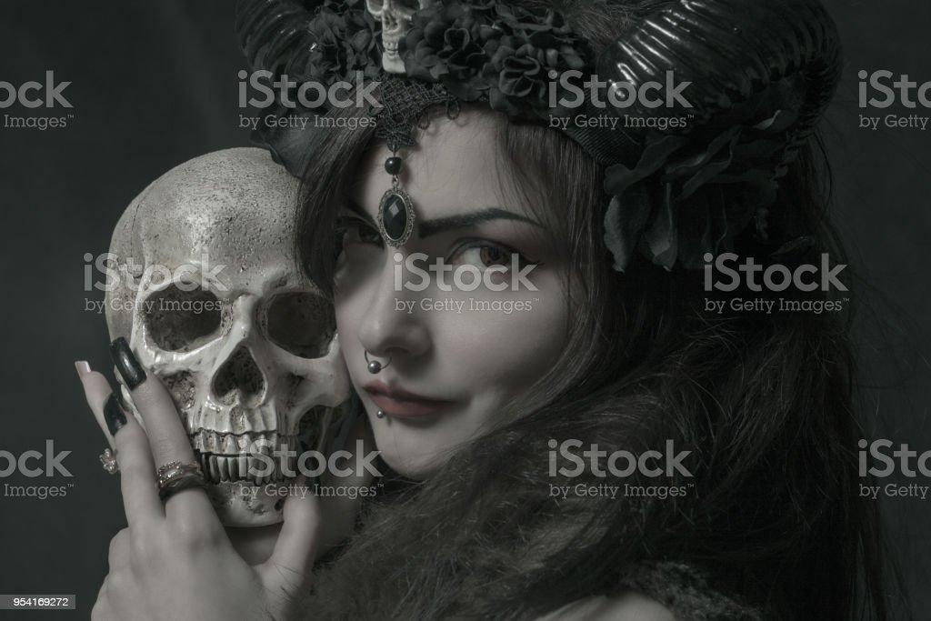 Horned asian girl with skull stock photo