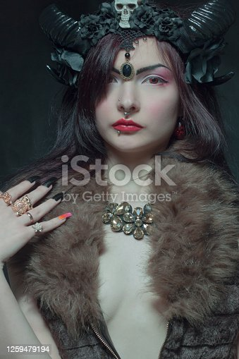 Pretty girl with horns  posing over dark background
