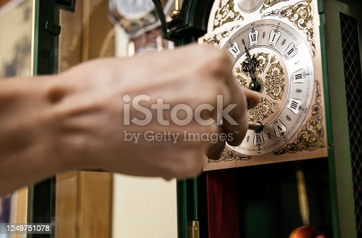White woman hand winding an antique fancy watch. Vintage clocks professional maintenance, fixing and caring concept dark background with negative space.