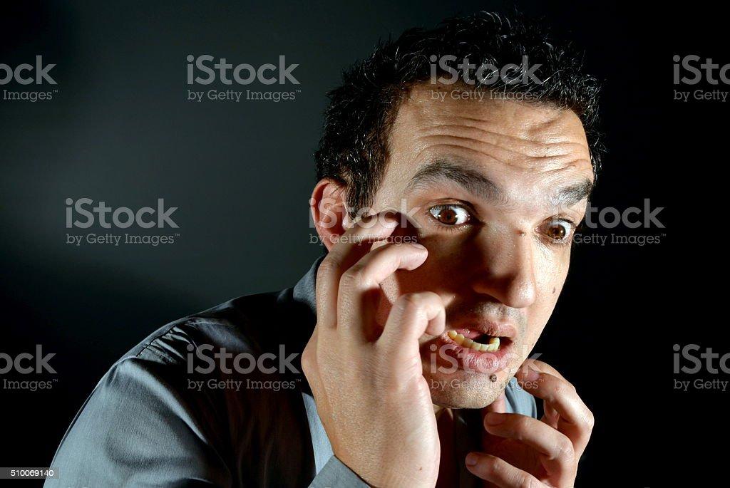 Shocked man looks down at something in a dark room