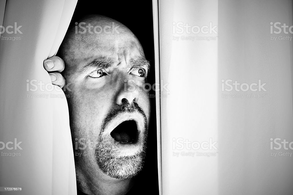 Horrified mature man looks sideways through curtains gasping in shock royalty-free stock photo