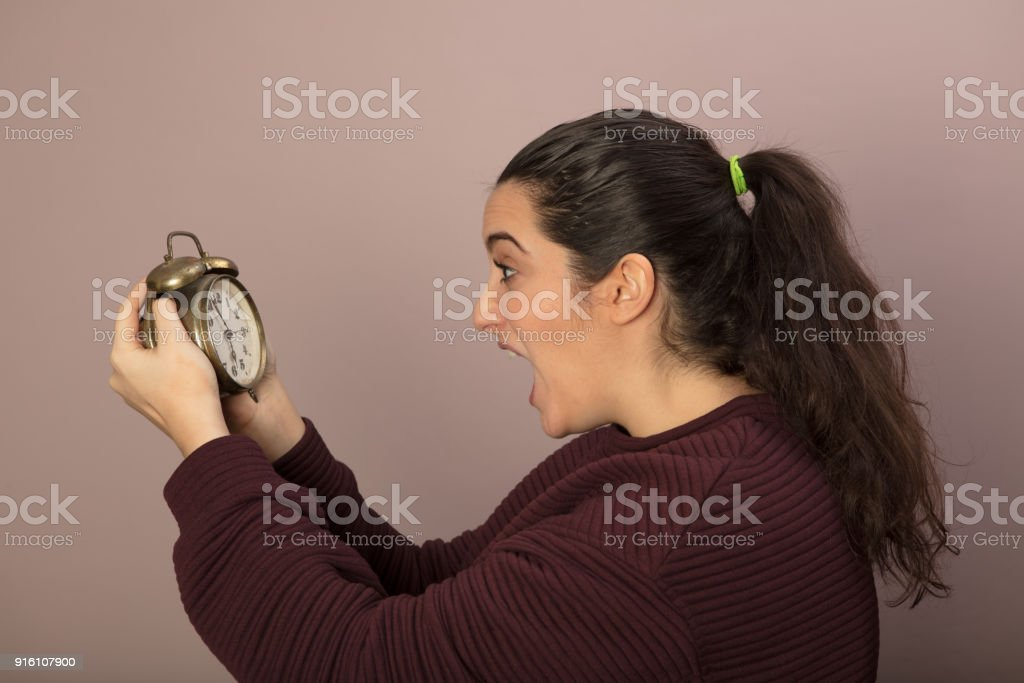 Horrified woman looking at the time stock photo
