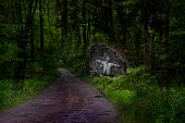 Horror. A figure in a gas mask and a shirt chained to a stone by the road in a dark forest.