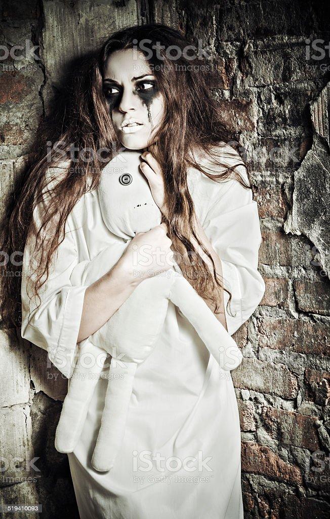 Cena de Horror: Estranho crazy garota com boneca moppet em mãos - foto de acervo