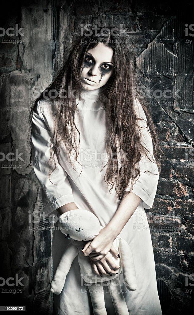 Cena de Horror: Estranho misterioso menina com boneca moppet em mãos - foto de acervo