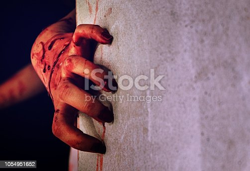istock Horror scene with a dirty hand with blood. 1054951652