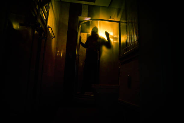 Horror silhouette of person in window. Scary halloween concept Blurred silhouette of witch in bathroom. Decorated with fireworks – zdjęcie