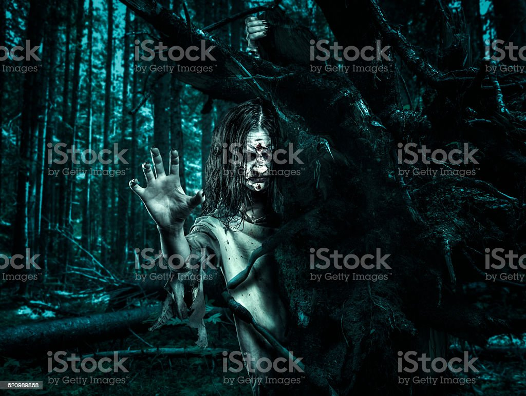 Horror undead woman looks out from behind a tree. foto royalty-free