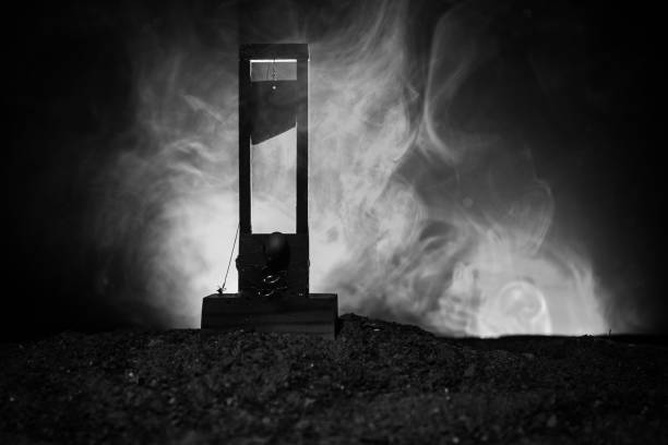 Horror view of Guillotine. Close-up of a guillotine on a dark foggy background. stock photo