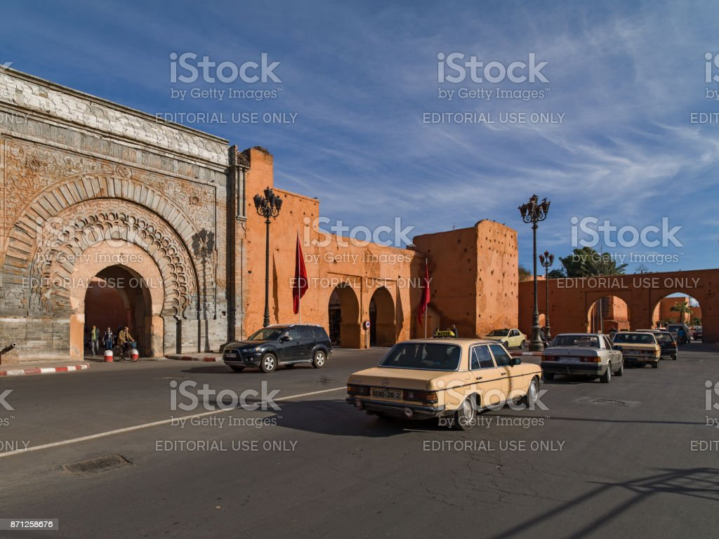 Horse and cars drawn carriage in front of one of the 19 gates of Marrakech, Bab Agnaou. Feb 06, 2014 stock photo