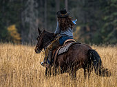 Female horseback rider going across a field. This was during a horse round-up photo shoot and the employees / riders have a great cowgirl look.