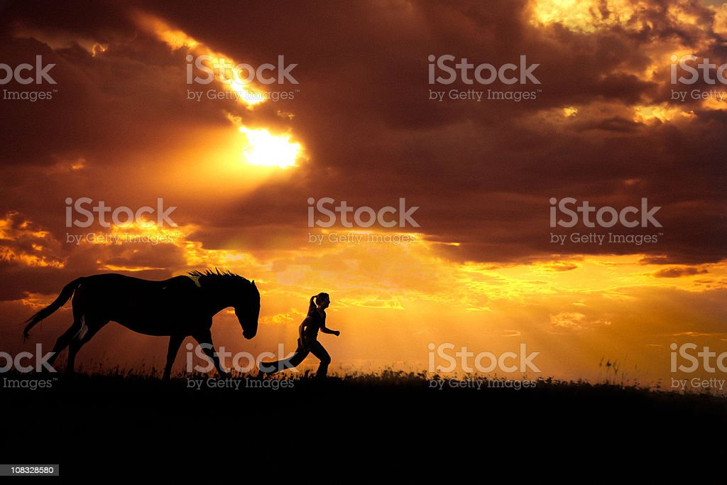 Horse And Girl Running At Sunset stock photo