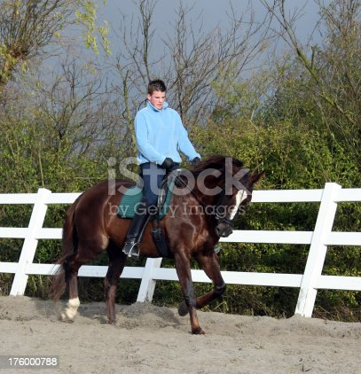 Image of boy cantering on his horse. What makes this picture rather special is the bad weather that turns the sky blue.