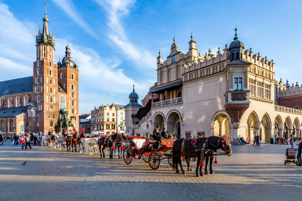 Horse carriages in front of Mariacki church on main square of Krakow stock photo