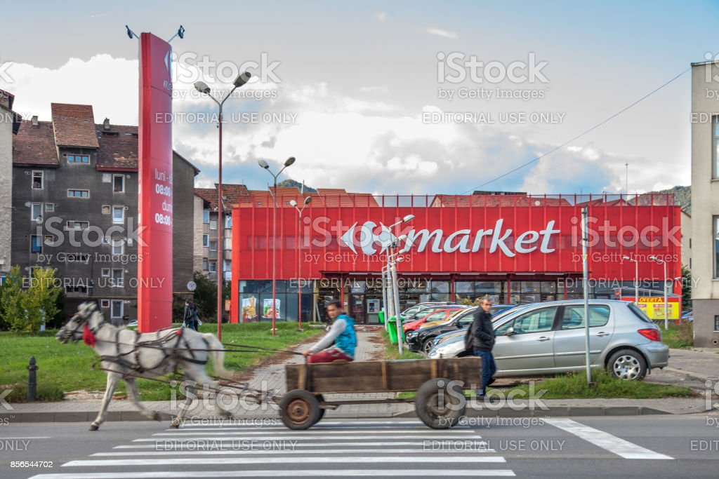 Horse Cart driven by people from Roma community passing in front of a Carrefour Market Supermarket. stock photo