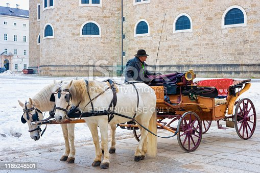 Salzburg, Austria - January 31, 2019: Horse fiaker on street with snow in Salzburg, Austria. Mozart city in Europe at winter. Carriage fiacre transport. Panoramic view and cityscape