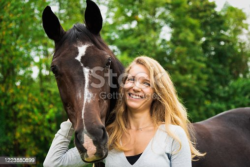 istock Horse Lovers Bright Smiling Young Woman Together with her Horse 1223880899