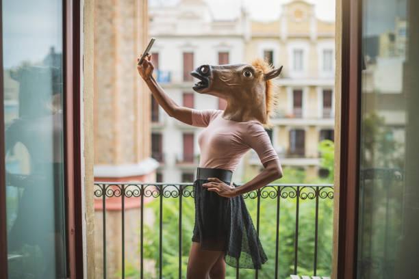 pferd maske frau selfie auf einem balkon - lustige pferde stock-fotos und bilder