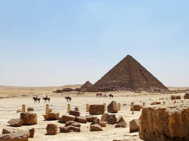 Horse riders in front of the pyramids stock photo