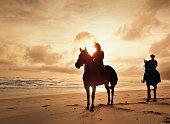 Horseback riding at the beach during sunrise in Myrtle Beach South Carolina. This is computer generated art from a photograph.