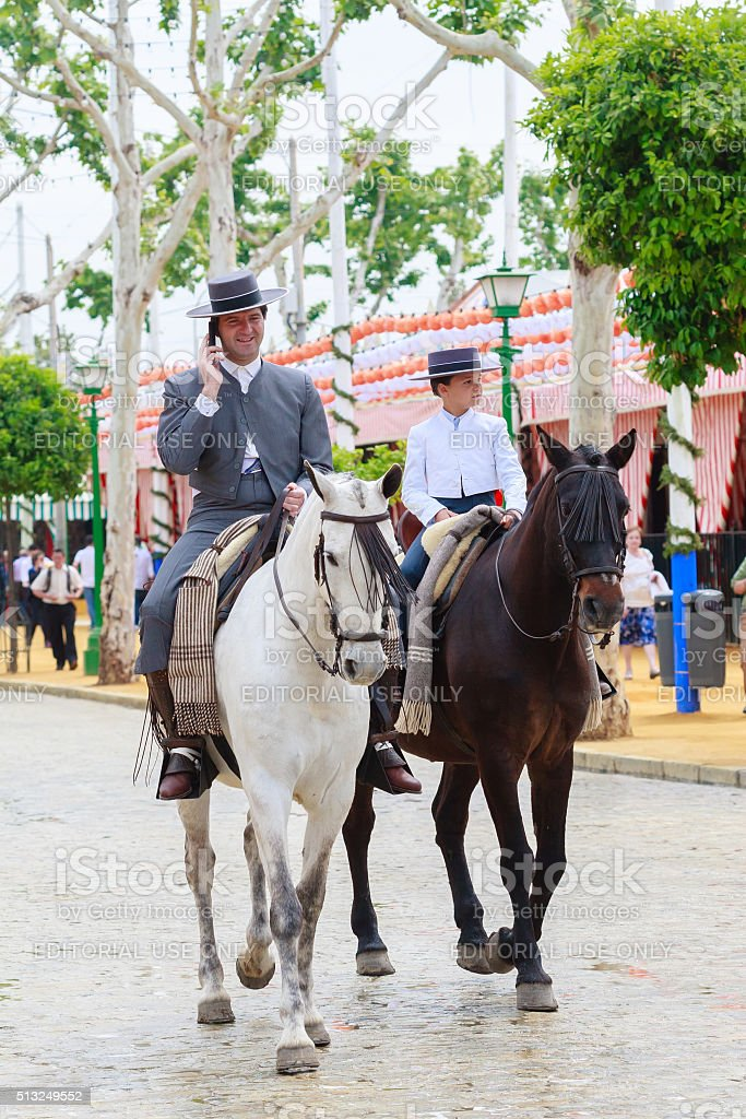Horse riders taking a walk by the fair of Seville stock photo