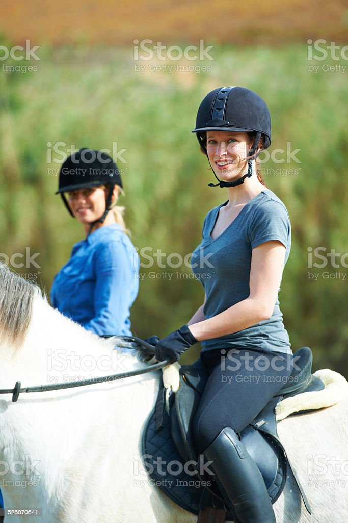 Portrait of two women sitting on their horses outside