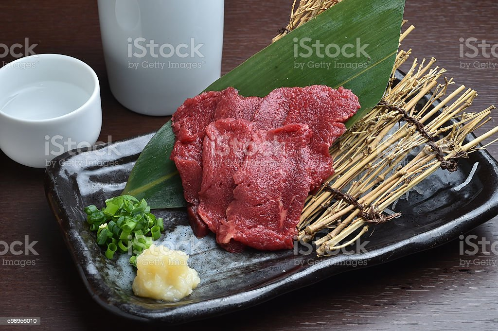 Horse sashimi and sake stock photo