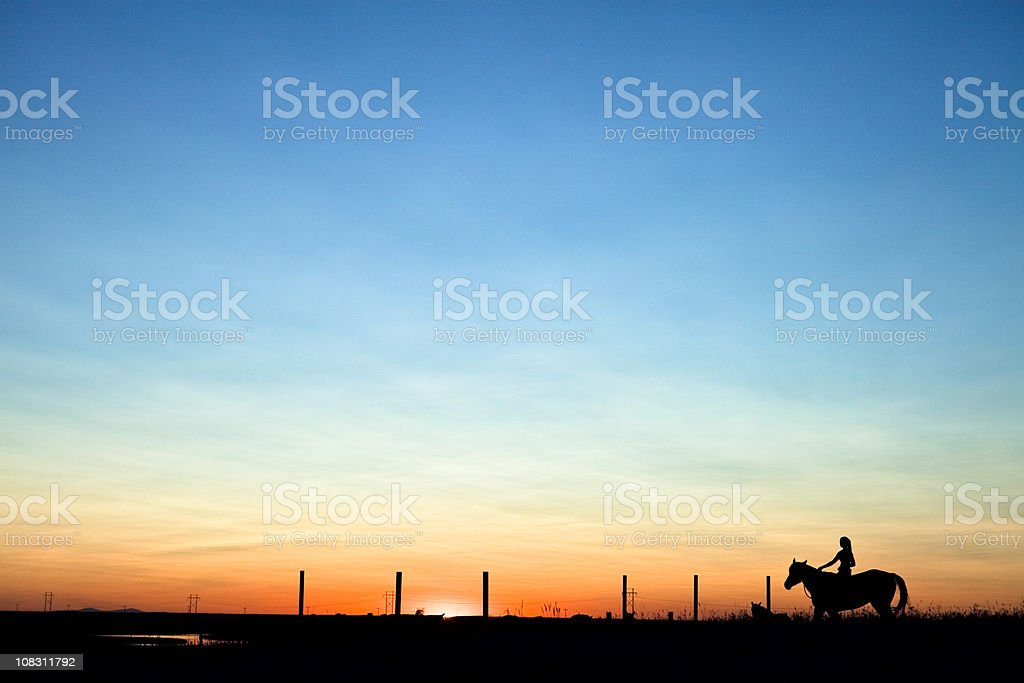 Horse & Woman Riding Into The Sunset stock photo