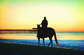 Silhouetted against vivid sunlight from a sinking sun breaking through winter clouds, a woman horseback rider walks her horse along the edge of the sandy beach.