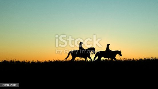 Two horseback riders on a grassy field with sunset in the background.