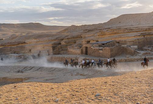 Horseback riders on the background of  Giza pyramids at sunset